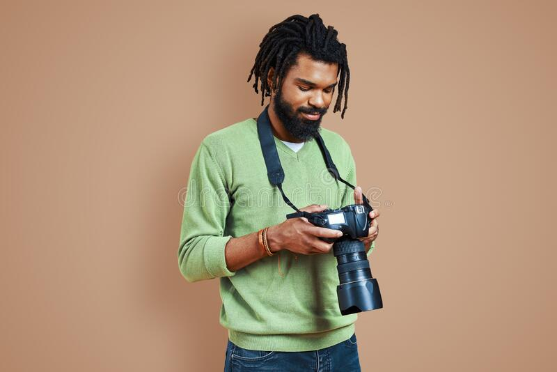 Handsome young African photographer in casual stock photos