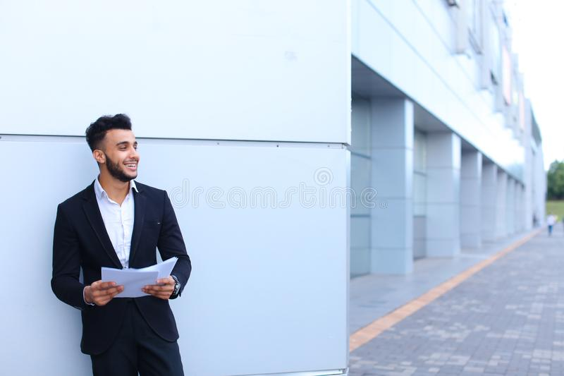 Handsome young Arab guy businessman smiling and looks away with papers in hand on background of business center. royalty free stock photos