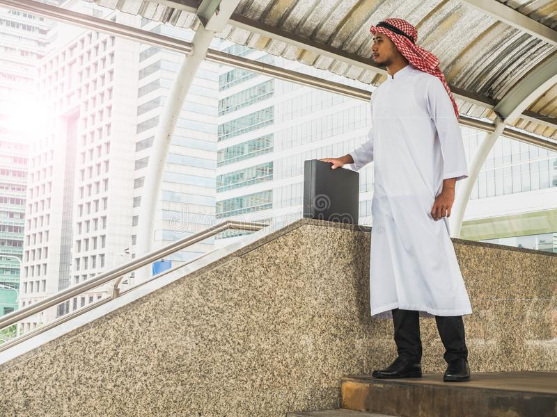 Handsome young arabic male, Middle east business man standing outdoor while looking for some direction stock images