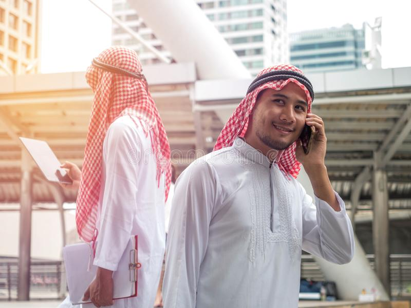 Handsome young arabic male texting on a mobile phone while traveling royalty free stock images