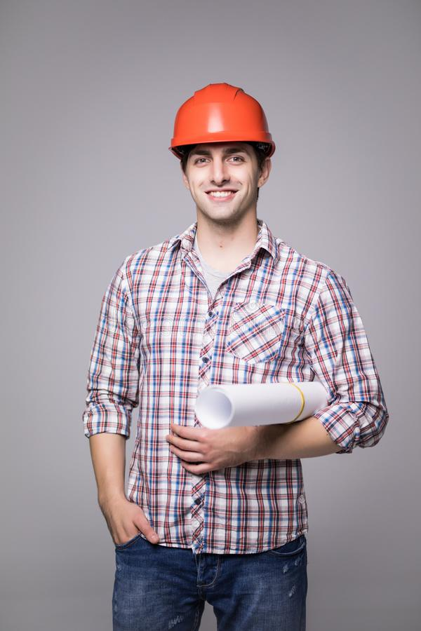 Handsome young architect in suit and protective helmet, looking at camera and smiling, on gray background royalty free stock photography