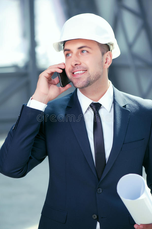 Handsome young architect is using telephone for royalty free stock images