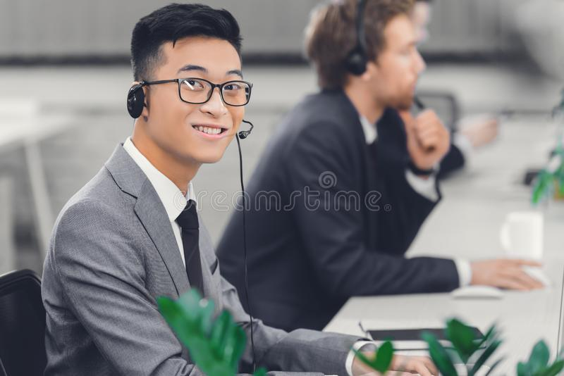 Handsome young asian businessman in headset smiling at camera while working stock photography