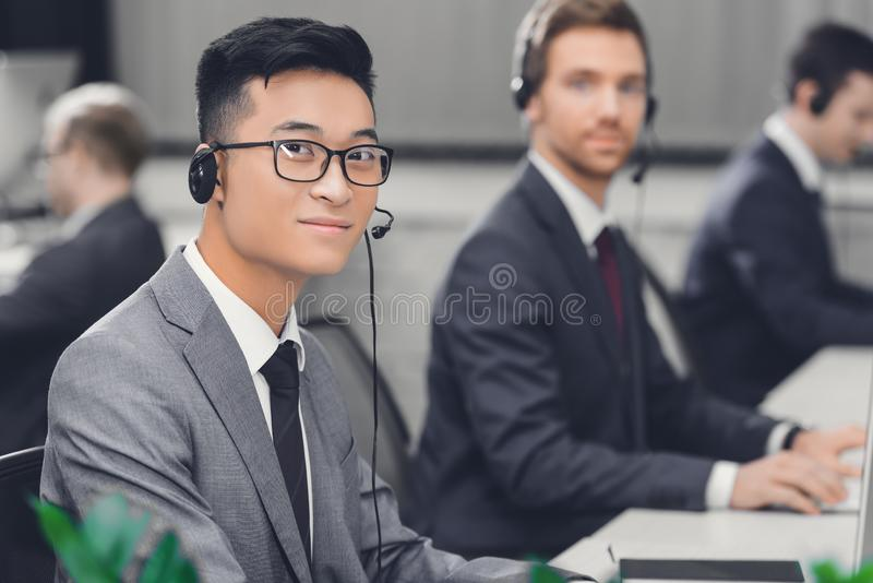 Handsome young asian businessman in headset smiling at camera while working with colleagues stock image