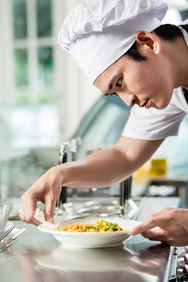 Handsome young Asian chef plating up food royalty free stock image