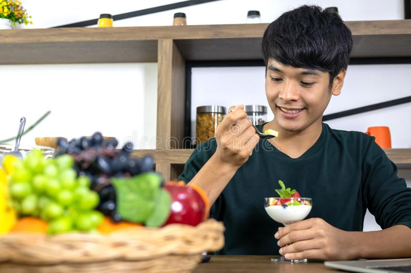 Handsome young men are happy to eat fruit yogurt. A handsome young Asian man is happy and is eating fruit yoghurt in the modern restaurant. Health care concept stock photo