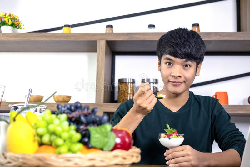 Handsome young men are happy to eat fruit yogurt. A handsome young Asian man is happy and is eating fruit yoghurt in the modern restaurant. Health care concept royalty free stock photos