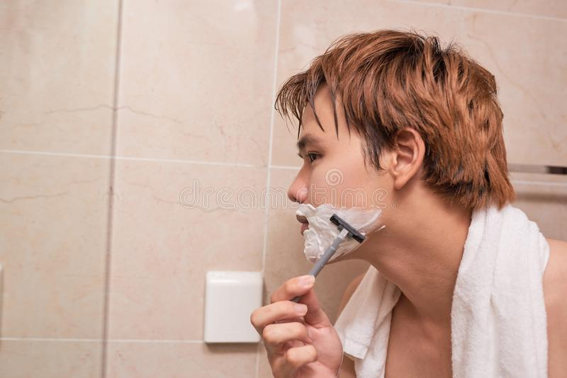 Handsome young asian man is shaving his face and looking at the royalty free stock photography