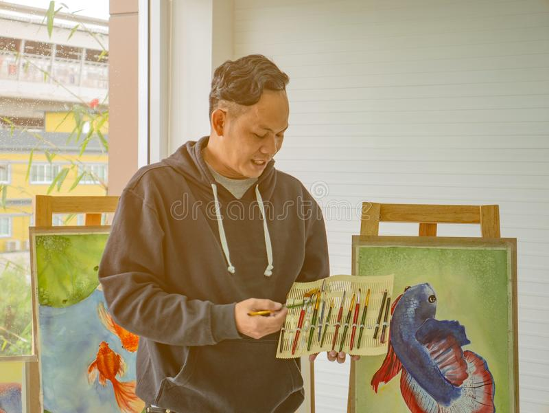 Handsome Young Asian man or water color artist Teaching how to paint royalty free stock photo
