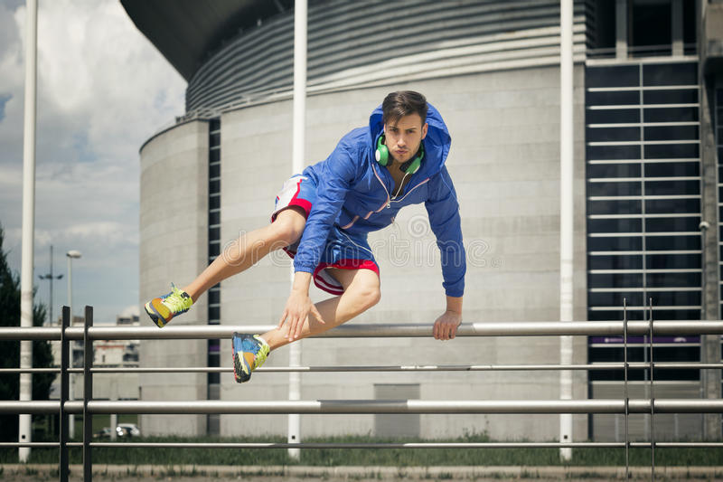 Handsome young athlete jumping over the fence royalty free stock photography