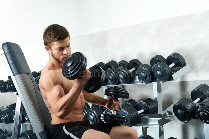 Handsome young athlete working out at the gym stock photos