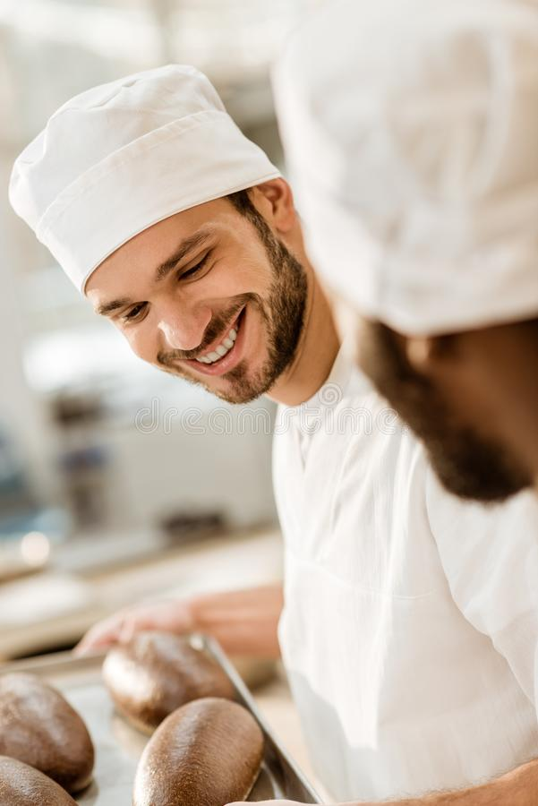 handsome young bakers in hats at baking manufacture looking at fresh rye bread loaves royalty free stock image
