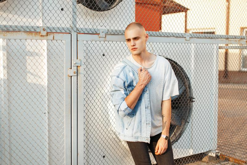 Handsome young bald man in a gray T-shirt and a denim jacket royalty free stock photo