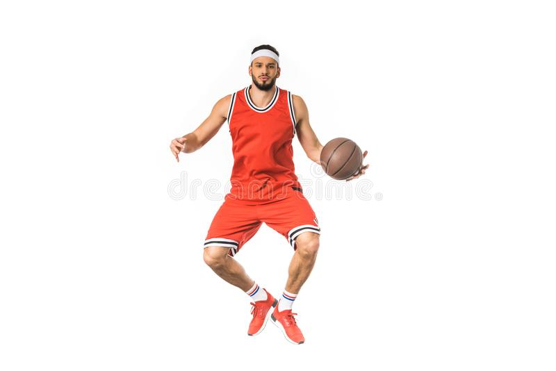 handsome young basketball player jumping with ball and looking at camera stock image