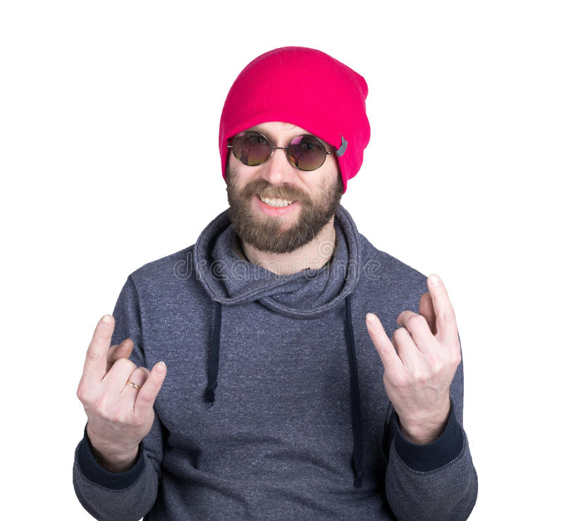 Handsome young bearded hipster in pink knitted hat expresses various emotions and shows different signs the fingers royalty free stock image