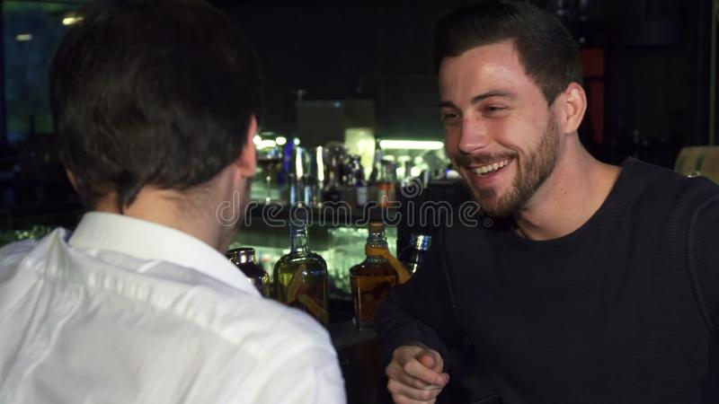 Young male friends talking while having drinks together at the bar stock image