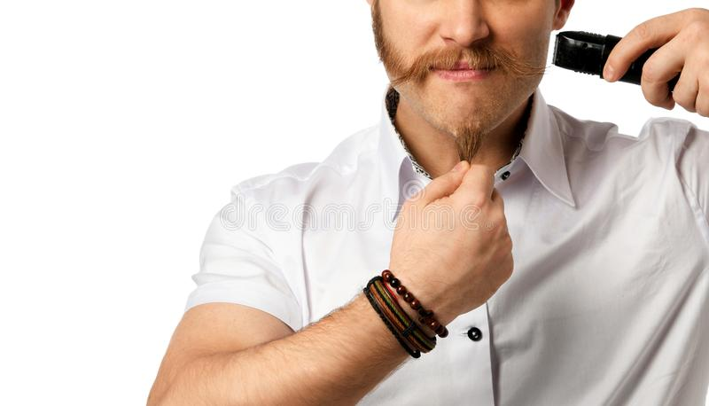 Handsome young bearded man trimming his beard with a trimmer  on a white royalty free stock photo