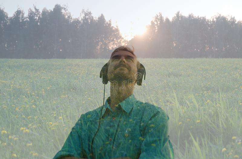 Handsome young bearded man wearing headphones and listen to relaxation music on nature on sunset. Double exposure. Sonic Therapy. royalty free stock image