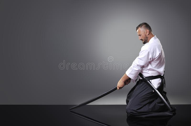 Handsome young black belt male karate posing with sword royalty free stock photo