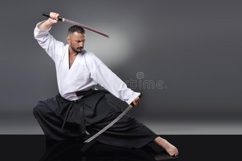 Handsome young black belt male karate posing with sword stock photography