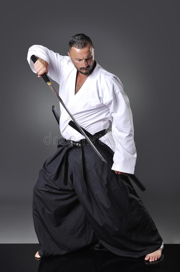 Handsome young black belt male karate posing with sword stock image