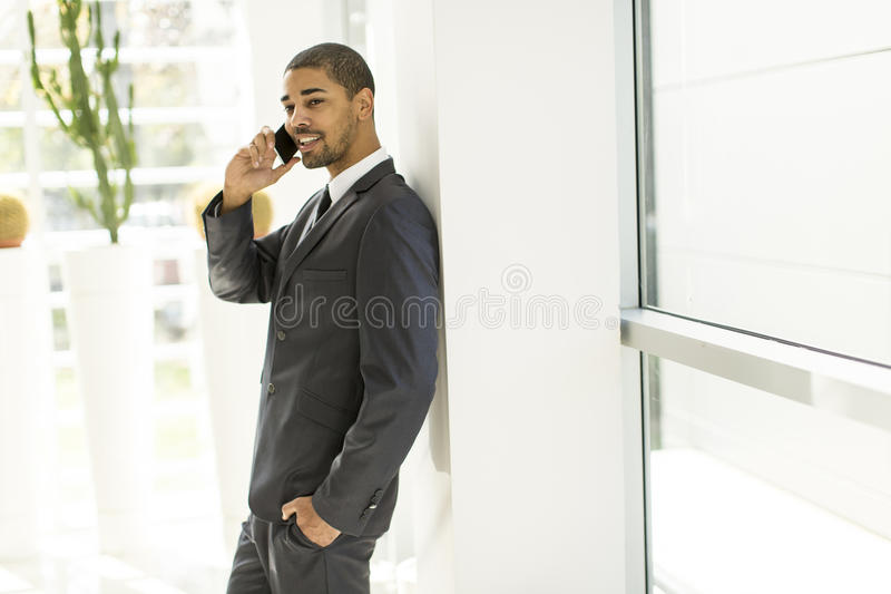 Handsome young black man with mobile phone stock image
