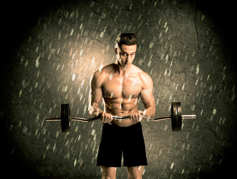 Fitness guy with weight showing muscles stock photo