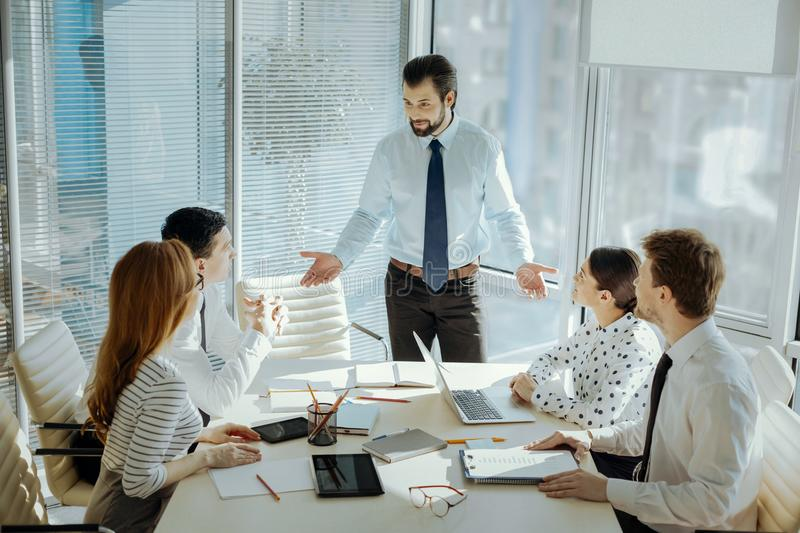 Handsome young boss carrying out business meeting stock image