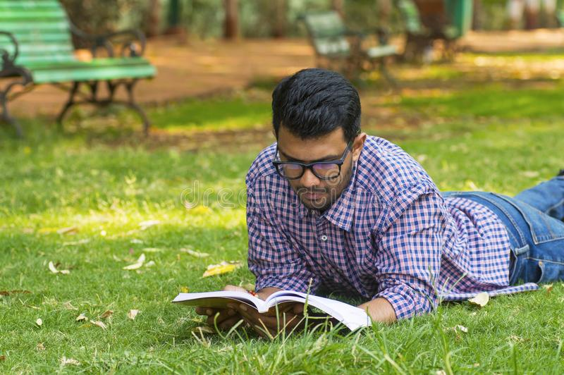 Handsome young boy reading while lying in park. Handsome young boy reading while lying on grass in park royalty free stock images