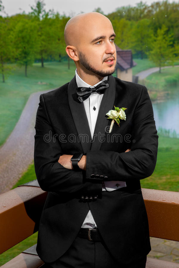 Handsome young bridegroom in black suit looking away royalty free stock photography
