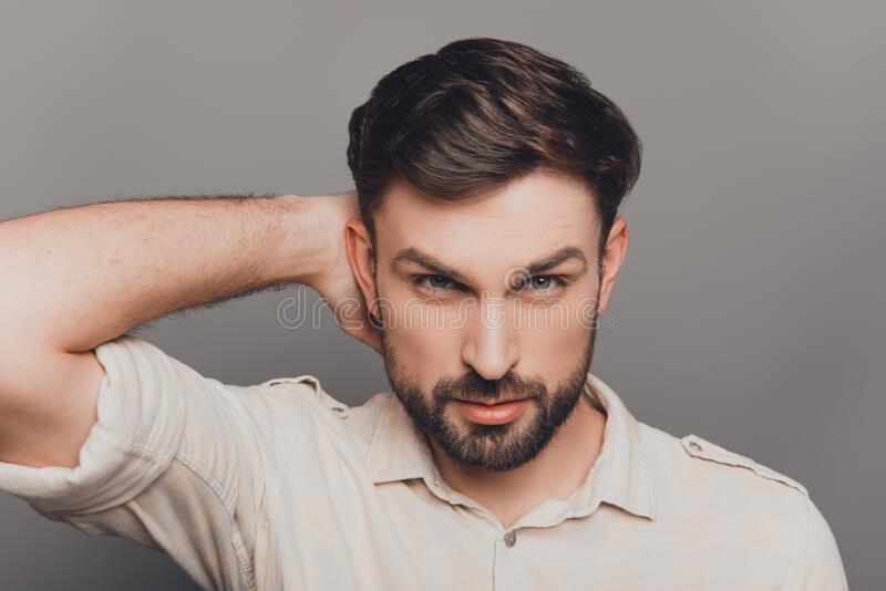 Handsome young brunet touching head and combining hair royalty free stock photography