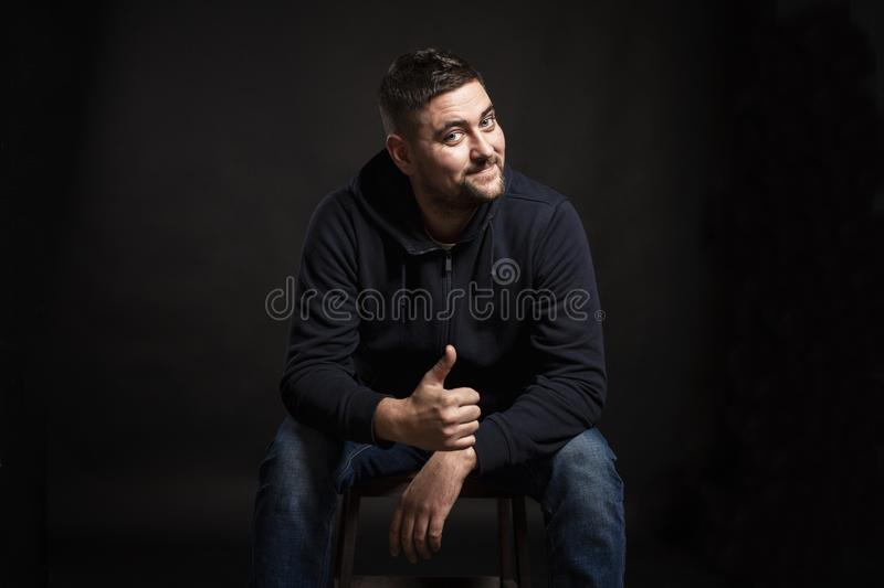 A handsome young brunette man with a beard is sitting on a chair, laughing and holding a thumb up. Black background royalty free stock photography
