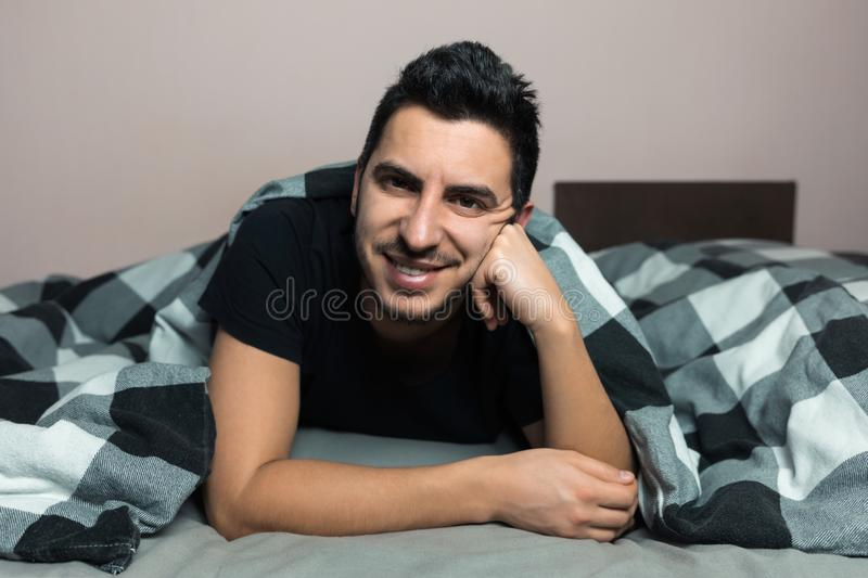 Handsome young brunette man is lying in bed. Smiling and looking at the camera royalty free stock photography
