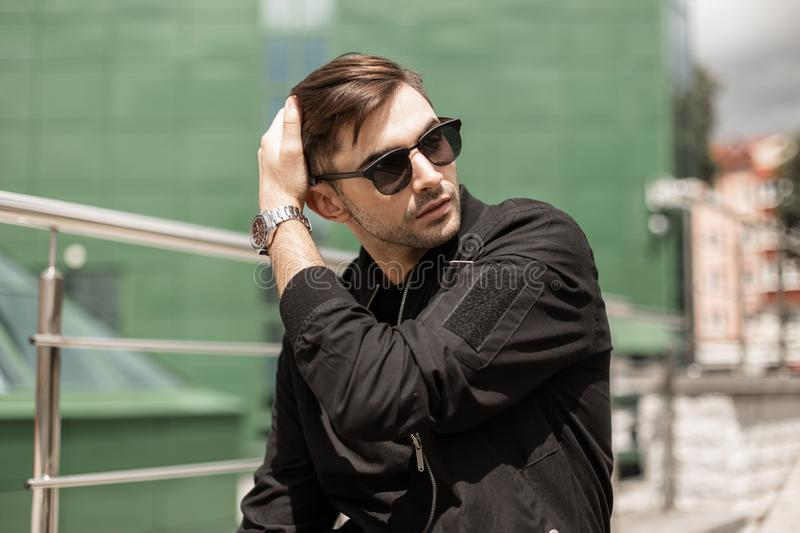 Handsome young brunette man with trendy hairstyle in vintage sunglasses in fashionable black jacket is resting in the city. On a sunny summer day. Attractive stock image