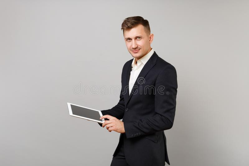 Handsome young business man in classic black suit holding, using tablet pc computer with blank empty screen isolated on stock image