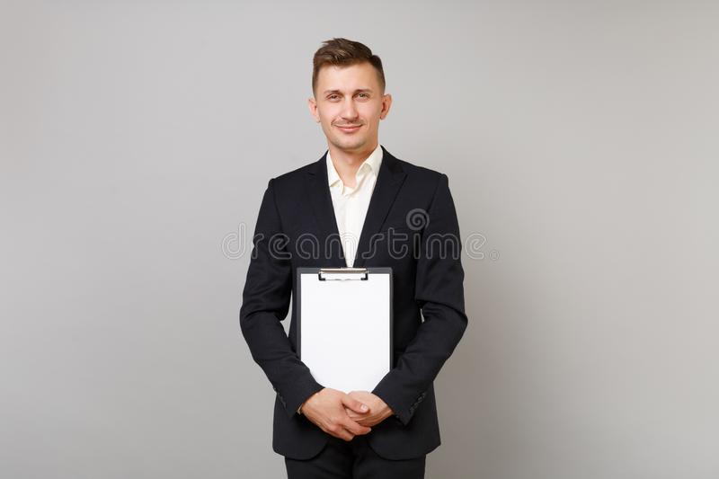 Handsome young business man in classic black suit, shirt holding clipboard with blank empty sheet workspace isolated on royalty free stock image