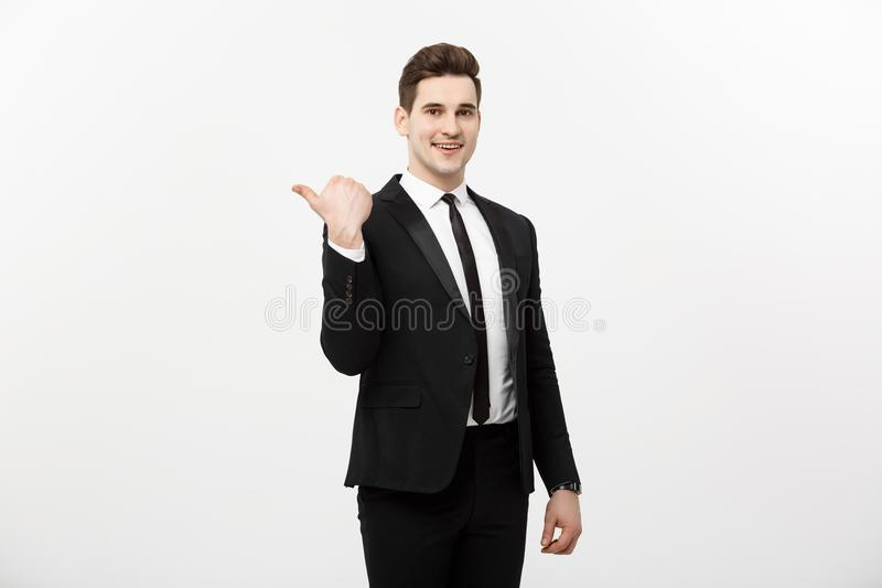 Handsome young business man happy smile point finger to empty copy space, businessman showing pointing side, concept of stock photography