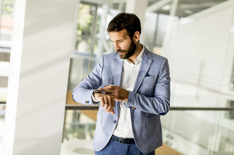 Handsome young business man is looking at his watch royalty free stock photos