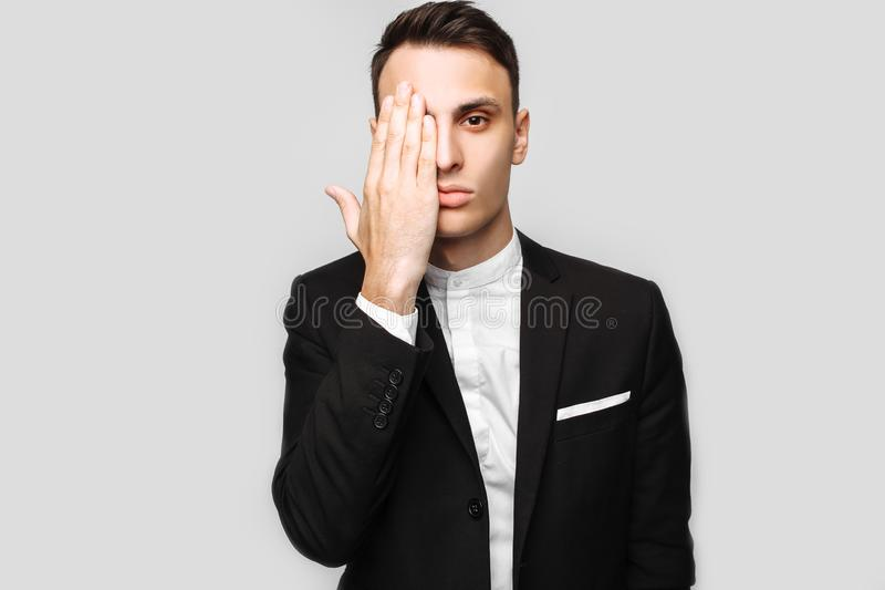 Handsome young business man, male, in a classic black suit, show royalty free stock photography