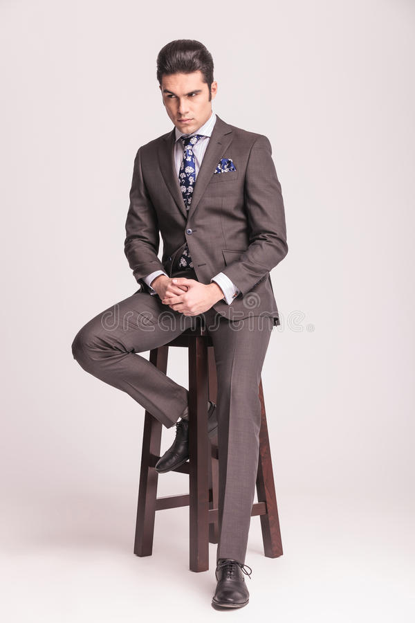 Handsome young business man sitting on a chair stock photography