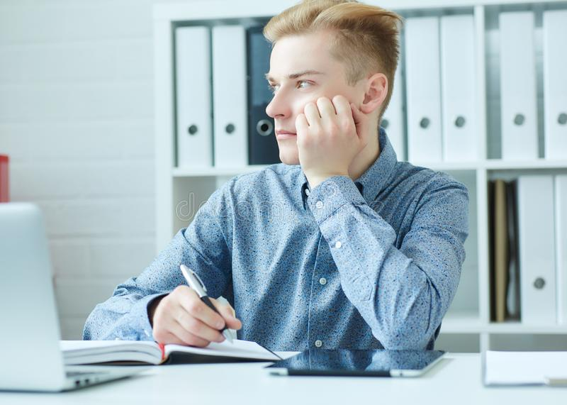 Handsome young business man sitting at the dask with laptop and looking at the window. stock photos