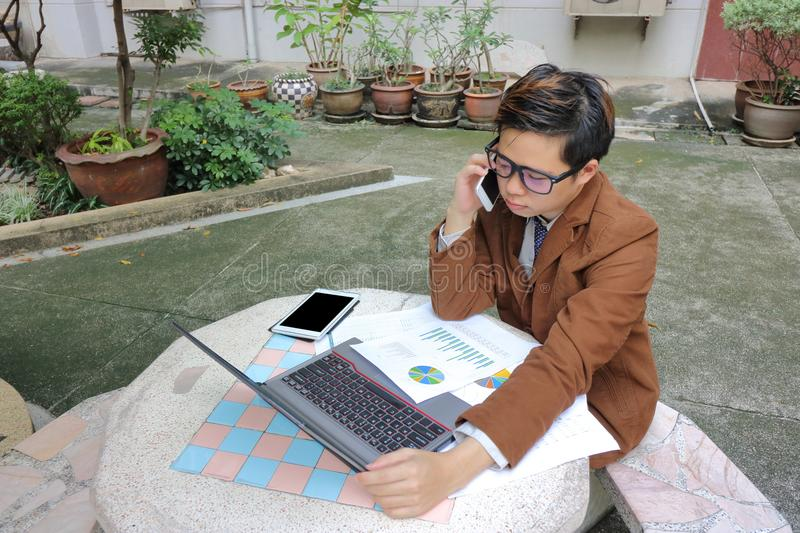 Handsome young business man talking on the phone with customer. stock photo