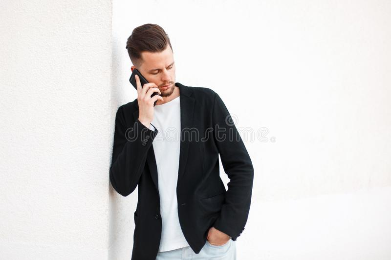 Handsome young business man talking on the phone near the white royalty free stock image