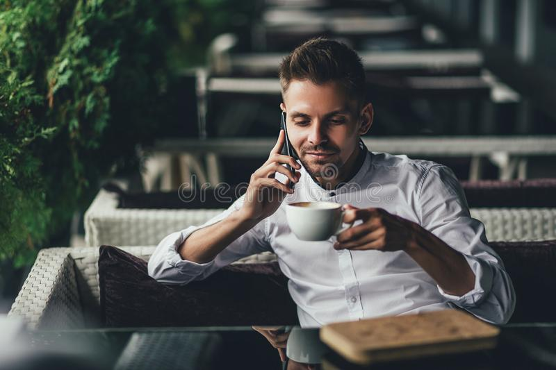 Handsome young business man, talking on the phone and smiling while a enjoying the cup of coffee in cafe royalty free stock photography