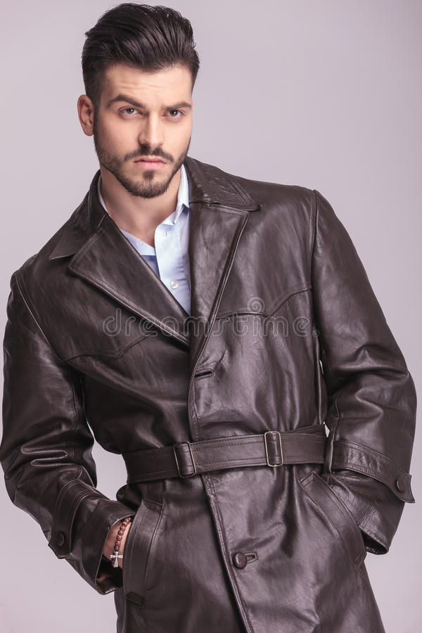 Handsome young business man wearing a brown leather coat. Looking away from the camera while holding both hands in his pockets stock photos