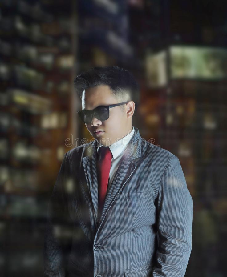Young business man wearing suit and red tie with sunglasses giving a sophisticated look at night. stock photography