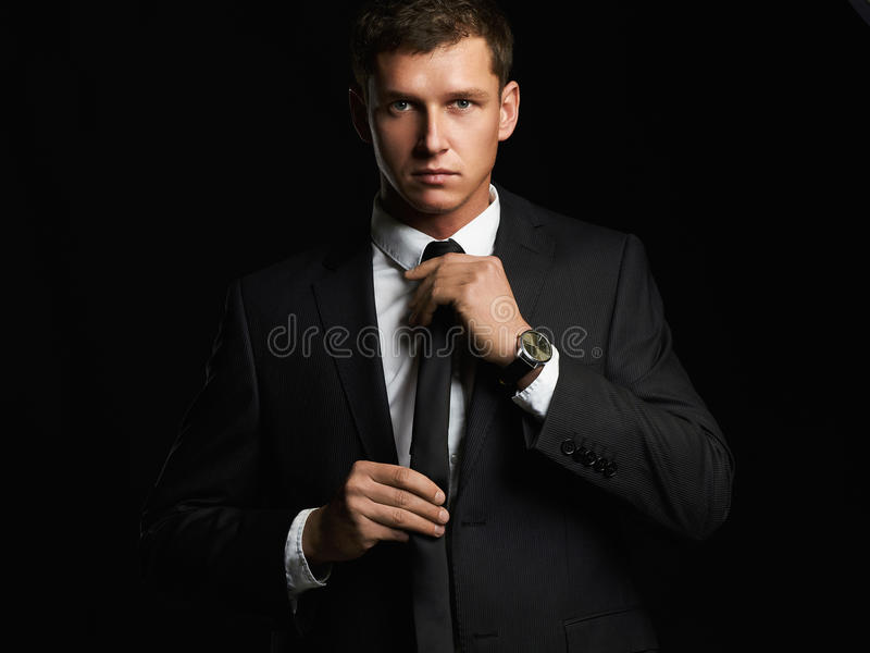 Handsome young businessman adjusting his tie. young man in suit stock images