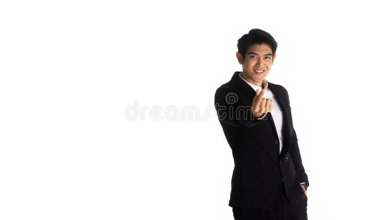 Handsome young businessman Asian caucasian wear a black suit with black hair, be a smile and standing poses by mini heart symbol. royalty free stock image