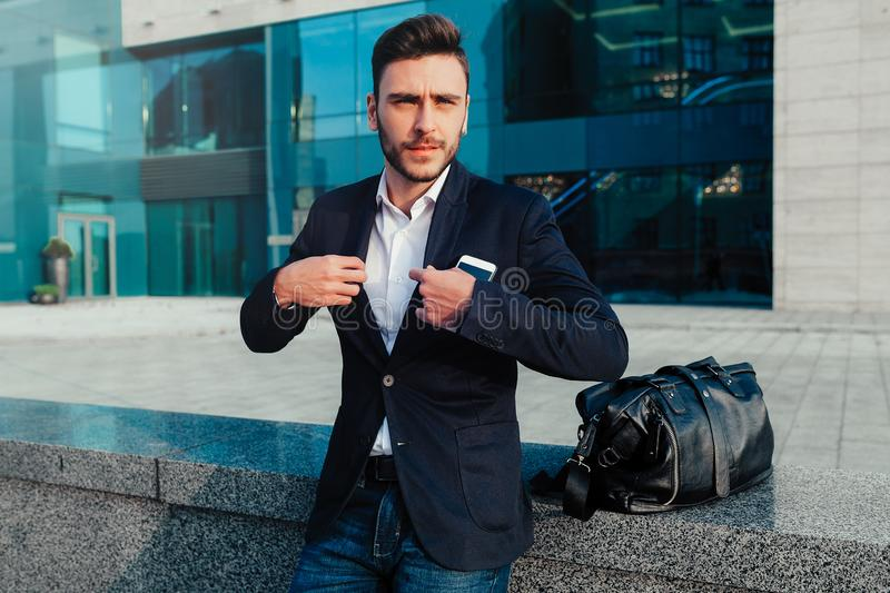 Handsome young businessman with a beard and in a business suit standing on the street against the background of the office stock image