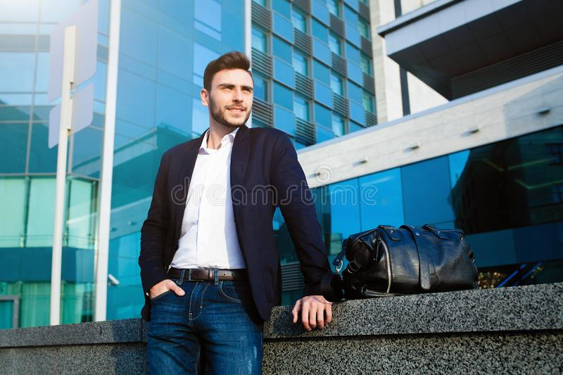 Handsome young businessman with a beard and in a business suit standing on the street royalty free stock photos